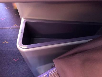 There is a large bin on the side of the seat that is very functional