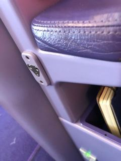 The headphone jack is located below the right armrest in the Business Class seat
