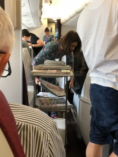 Flight attendant distributing papers to Business Class passengers and we were also offered newspapers prior to departure