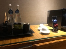 There is a coffee machine on top of the mini-bar