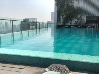 There are a number of suntan chairs at the infinity pool