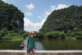 My friend at the bridge with the stunning view of the limestone mountains