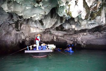 Paddling through Luon Cave under the limestone island