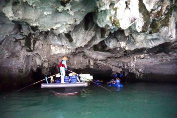 Paddling through Luon Cave under the limestone island