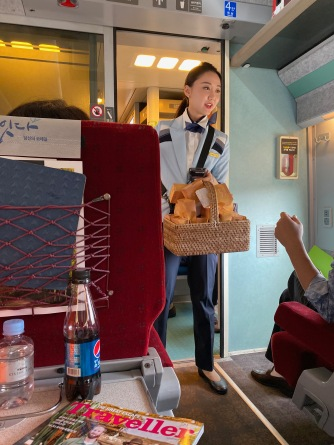 Train attendants doing her round distributing snacks for First Class passengers